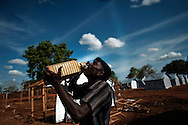A man drinks water as he helps to construct temporary structures for people displaced by the war between the government of Sri Lanka and the LTTE at a camp for internally displaced people at the Menick farm near Vavuniya, Sri Lanka on July 8, 2009.Nearly 300,000 people remain in camps after the war as the government works on resettling them and screening for remaining LTTE members.