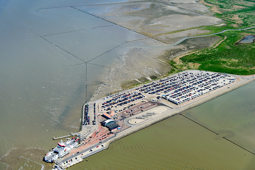 Nederland, Friesland, Gemeente Dongeradeel, 07-05-2018; Veerdam voor de veerboot naar Ameland met parkeerterrein voor langparkeerders ter hoogte van Holwerd (Holwert). Explotatie door Wagenborg passagiersdiensten. Friesche Wad met kweldergebied en buitendijkse polder van Noorderleeg (Noarderleech) ook Noard-Fryslan Butendyks.<br /> Causeway for the ferry to Ameland. Land reclamation, Noorderleeg (Northern Void), polder and salt marsh area outside the dikes. The so-called salt marsh works consist of square sections, bordered by brushwood breakwaters causing the sludge to settle. <br /> luchtfoto (toeslag op standard tarieven);<br /> aerial photo (additional fee required);<br /> copyright foto/photo Siebe Swart