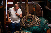 A fishermen looks at rope, nets and tackle in his home port of Tarbert on the western Scottish Mull of Kintyre, a quiet community in the western Isles. Inhaling on his pipe, the middle-aged man is surrounded by the equipment that keeps his fishing business at sea to prive him with a livelihood. The boat is rusty, having seen many miles on inland seas around the western isles, the edge of the Atlantic, dependent of fisheries policy and EU quotas that dictate how much they're allowed to catch per day/per week.