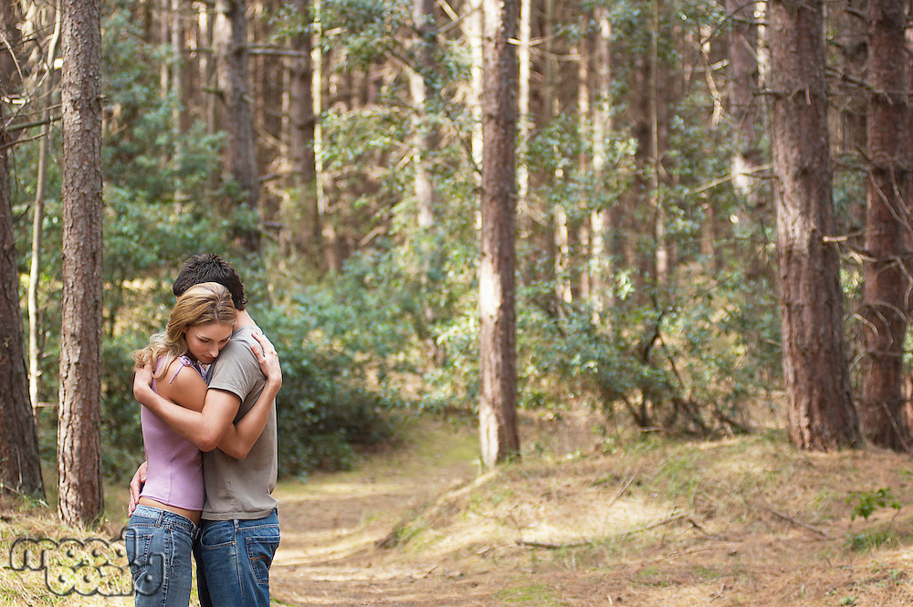 Couple standing on forest trail Hugging side view