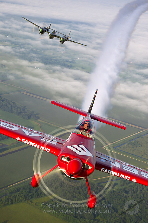 Greg Poe flies his bright red high performance MX2 sponsored by Fagen Inc., an alterative fuel company, behind Larry Kelley's B-25 Panchito over the lush countryside near Oshkosh, Wisconsin. Approaching from the rear is Rob Ator in P-38 'Ruff Stuff'.