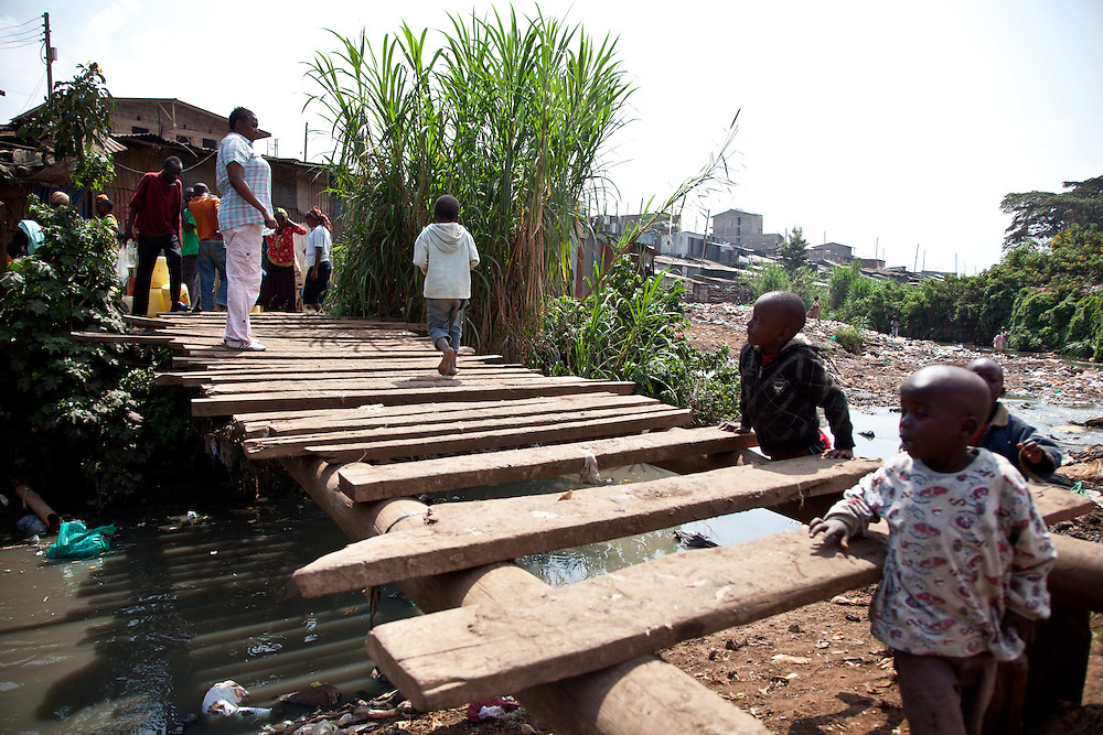 Young children play on one of only three bridges that connects communities together across the Mathare River. The hand constructed bridge seems to be haphazardly constructed and could be dangerous to the unfamiliar pedestrian.