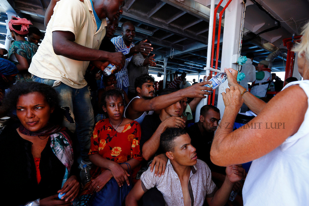 Migrants on the lower deck of the Migrant Offshore Aid Station (MOAS) ship MV Phoenix reach out for bottles of water after being rescued from an overloaded wooden boat 10.5 miles off the coast of Libya August 6, 2015.  An estimated 600 migrants on the boat were rescued by the international non-governmental organisations Medecins san Frontiere (MSF) and MOAS without loss of life on Thursday afternoon, according to MSF and MOAS, a day after more than 200 migrants are feared to have drowned in the latest Mediterranean boat tragedy after rescuers saved over 370 people from a capsized boat thought to be carrying 600.<br /> REUTERS/Darrin Zammit Lupi <br /> MALTA OUT. NO COMMERCIAL OR EDITORIAL SALES IN MALTA