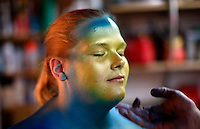 """Gabi Jones is inspected by airbrush artist David Brawner as he painted her as a piece of """"bodyart"""" in a garage studio in a Denver suburb April 13, 2010.  Jones (not her real name) at 502 pounds is a size acceptance advocate who says she wanted to be painted """"...to push the envelope on what a big person can do and break the molds of what is accepted in society.""""  REUTERS/Rick Wilking  (UNITED STATES)"""