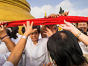 30 OCTOBER 2014 - BANGKOK, THAILAND: People carry the red cloth around the chedi during the parade marking the start of the annual temple fair at Wat Saket. Wat Saket is on a man-made hill in the historic section of Bangkok. The temple has golden spire that is 260 feet high which was the highest point in Bangkok for more than 100 years. The temple construction began in the 1800s in the reign of King Rama III and was completed in the reign of King Rama IV. The annual temple fair is held on the 12th lunar month, for nine days around the November full moon. During the fair a red cloth (reminiscent of a monk's robe) is placed around the Golden Mount while the temple grounds hosts Thai traditional theatre, food stalls and traditional shows.   PHOTO BY JACK KURTZ