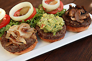 Three mini hamburgers with onions, guacamole and mushrooms