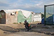 Calais, Pas-de-Calais, France - 16.10.2016    <br />     <br />  A refugee brush his teeth  in front of a booth with the slogan British Hotel in the &rdquo;Jungle&quot; refugee camp on the outskirts of the French city of Calais. Many thousands of migrants and refugees are waiting in some cases for years in the port city in the hope of being able to cross the English Channel to Britain. French authorities announced that they will shortly evict the camp where currently up to up to 10,000 people live.<br /> <br /> Ein Fluechtling putzt sich die Zaehne vor einer Huette mit der Aufschrift &quot;British Hotel&quot; im &rdquo;Jungle&rdquo; Fluechtlingscamp am Rande der franzoesischen Stadt Calais. Viele tausend Migranten und Fluechtlinge harren teilweise seit Jahren in der Hafenstadt aus in der Hoffnung den Aermelkanal nach Gro&szlig;britannien ueberqueren zu koennen. Die franzoesischen Behoerden kuendigten an, dass sie das Camp, indem derzeit bis zu bis zu 10.000 Menschen leben K&uuml;rze raeumen werden. <br /> <br /> Photo: Bjoern Kietzmann