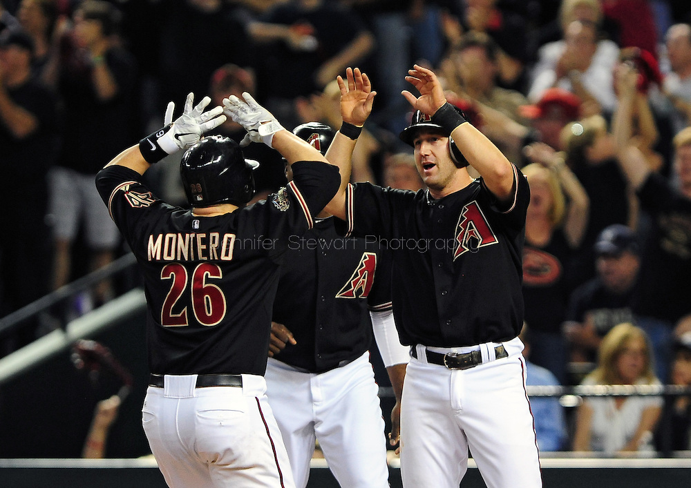 Oct. 5 2011; Phoenix, AZ, USA; Arizona Diamondbacks catcher Miguel Montero (26) is congratulated by teammate Willie Bloomquist (18) celebrate after scoring during the first inning against the Milwaukee Brewers at game four of the 2011 NLDS at Chase Field. The Diamondbacks defeated the Brewers 10-6.  Mandatory Credit: Jennifer Stewart-US PRESSWIRE.