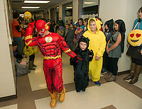 "Caden Tucker  ""Flash"" leads his group through the halls at Pleasant Street School during the Halloween Parade on Friday afternoon.  (Karen Bobotas/for the Laconia Daily Sun)"