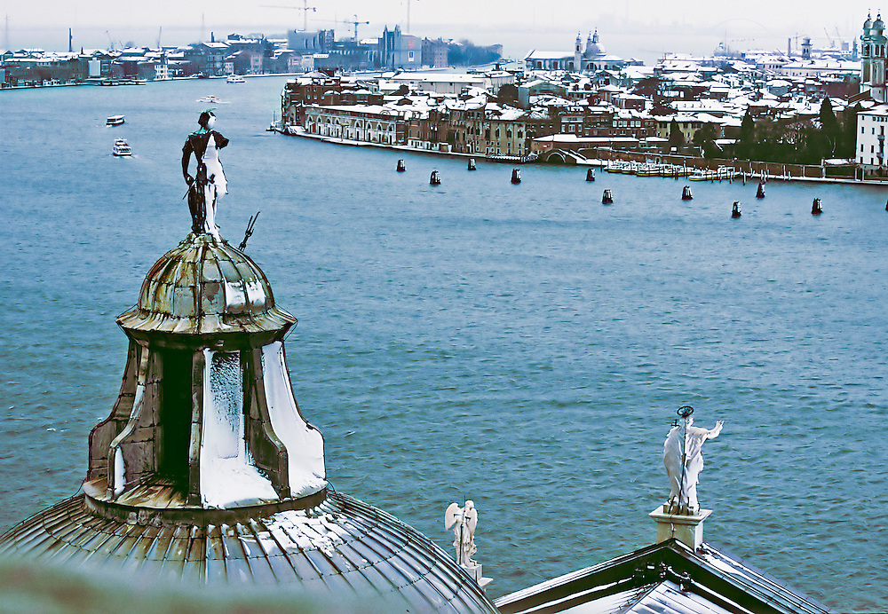 View of Venice under snow from the top of the campanile of San Giorgio Maggiore.  The statue of the saint atop the church dome is in the foreground.