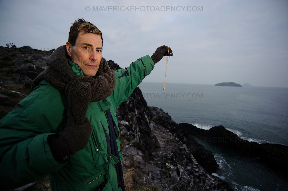 """NORTH BERWICK, UK - 6th March 2010:  Mystifier Uri Geller sets foot on Lamb island, a tiny island which is believed to be connected with the Great Pyramids of Giza, in search of treasure left behind by an exiled Egyptian Princess """"Scota"""".  Uri bought the tiny island which is situated just off North Berwick, in the Firth of Forth after his friend Mohammed Al Fayed republished """"Abbot of Inchcolm"""" a 15th Century document linking the islands to ancient Egypt. Pictured Uri uses a pendant to search for treasure on the island.   (Photograph: Callum Bennetts/MAVERICK)"""