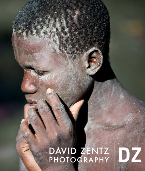 A boy stands covered in dry mud in St. Jacques' hole, a mud pit on the edge of the village of Plaine du Nord, Haiti, on July 24, 2008. Pilgrims arrive at the site every July to worship the lwa Ogou, who presides over matters of war, politics, fire and iron, as well as St. James, the Catholic warrior saint.