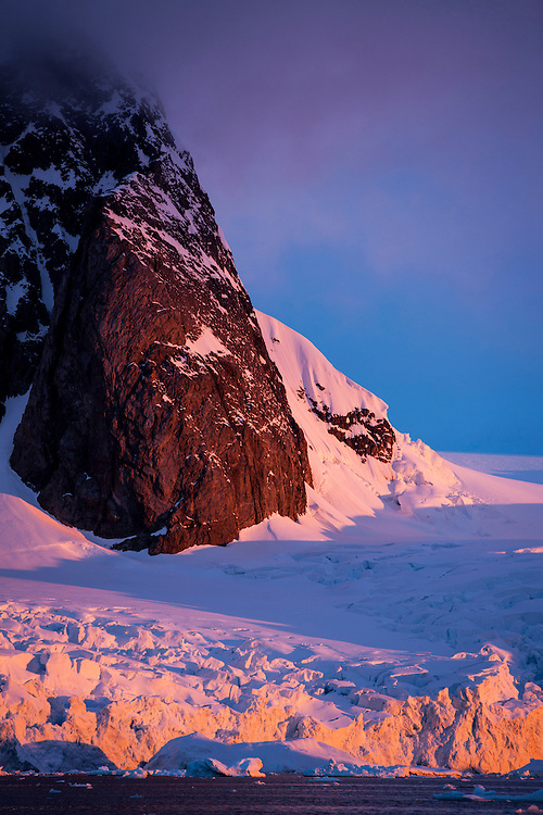Antarctica, Petermann Island, Setting midnight sun lights mountain peak and glaciers along Lemaire Channel