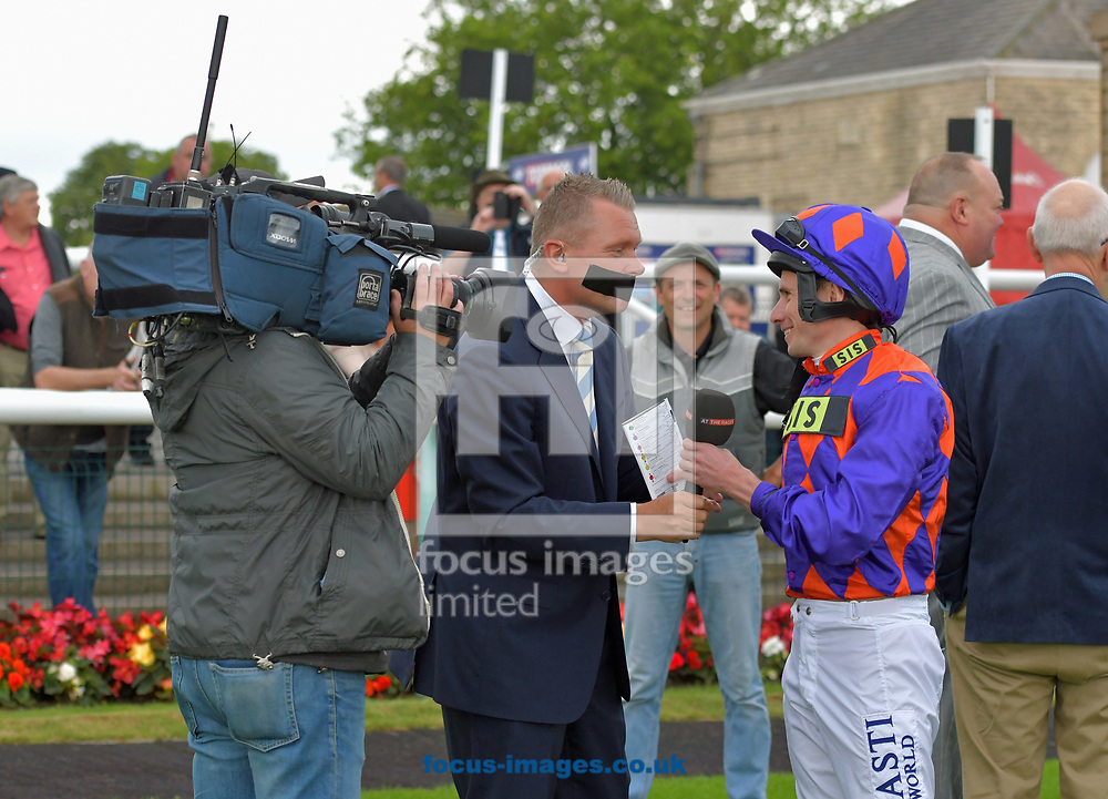 Horse racing presenter Matt Chapman with his mouth covered by gaffer tape to raise money for Voice Of Racing Charity day interviews jockey Ryan Moore before race 1 at the 188 Bet Summer Afternoon meeting at Doncaster Racecourse, Doncaster<br /> Picture by Martin Lynch/Focus Images Ltd 07501333150<br /> 30/06/2017