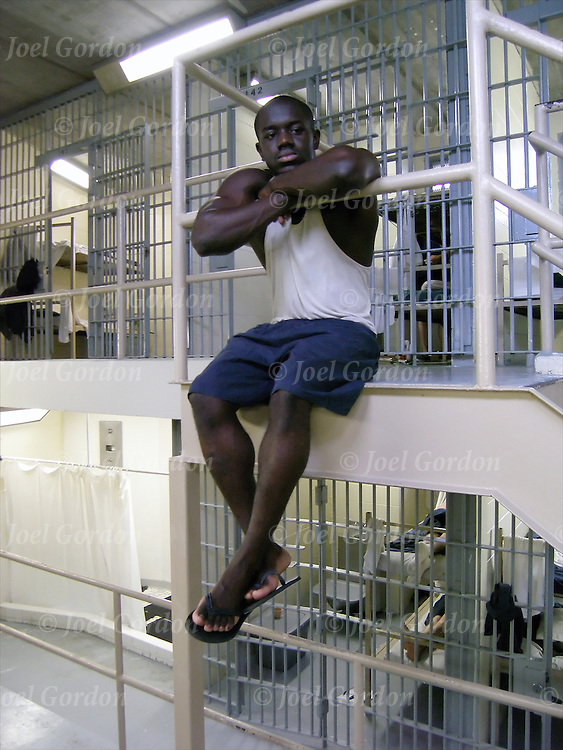 African American Inmate sitting down outside of cell in the POD, lost in his thoughts.