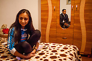 Portrait of 22 years old Roma student Cornelia Budrega in the house of her parents. She is is studying Commercial Business Administration in a Master Degree Program in Bucharest and never experienced any kind of discrimination because of being a Roma. In the mirror Roma activist Marius Tudor.