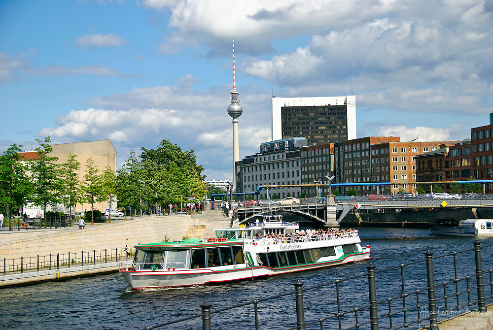 A tourist boat on the Spree River in Berlin, Germany with the Fernsehturm visible in the background.