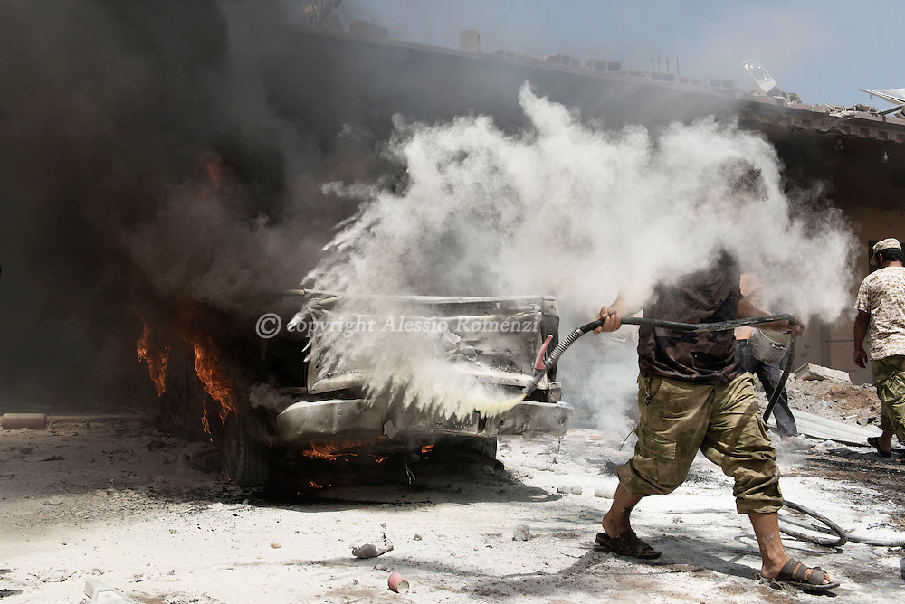 Libya, Sirte: A man wields an extinguisher after two explosions of SBVIED (Suicide-Born Vehicle Improvised Explosive Device) that killed at least 10 and injured 30 fighters sympathising with Libya's Government of National Accord's (GNA). Alessio Romenzi