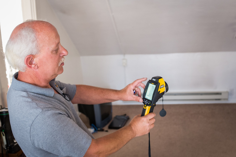 Mike Lehman explains the use of a thermal camera inside the attic apartment at 86 West State Street during an energy audit Wednesday, June 24, 2015.  Photo by Ohio University  /  Rob Hardin