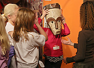 Nyah Chamberlain, 9, of Westfield Elementary School tries on a mask in the Endless Possibilities exhibit at the African American Museum of Iowa in Cedar Rapids on Friday, March 22, 2013.