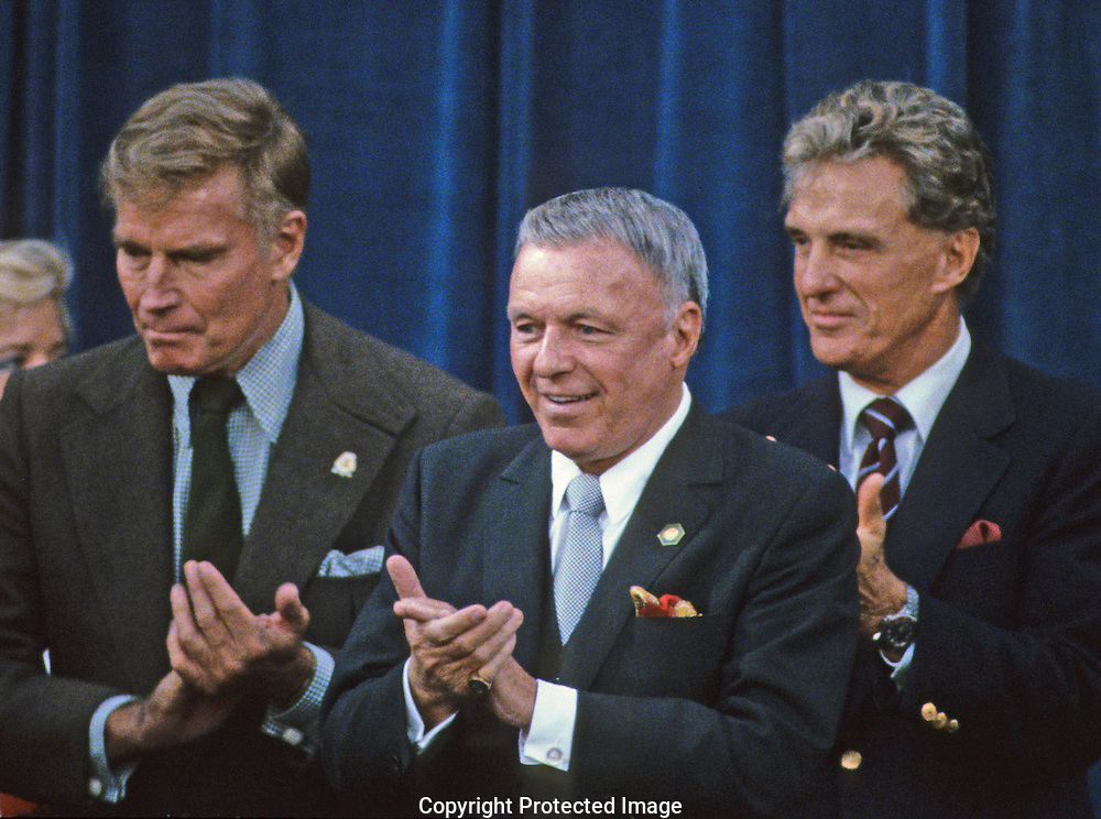 .Frank Sinatra, Charleton Heston, Robert Stack clap at an Inauguration event in January 1985..Photograph by Dennis Brack bb30