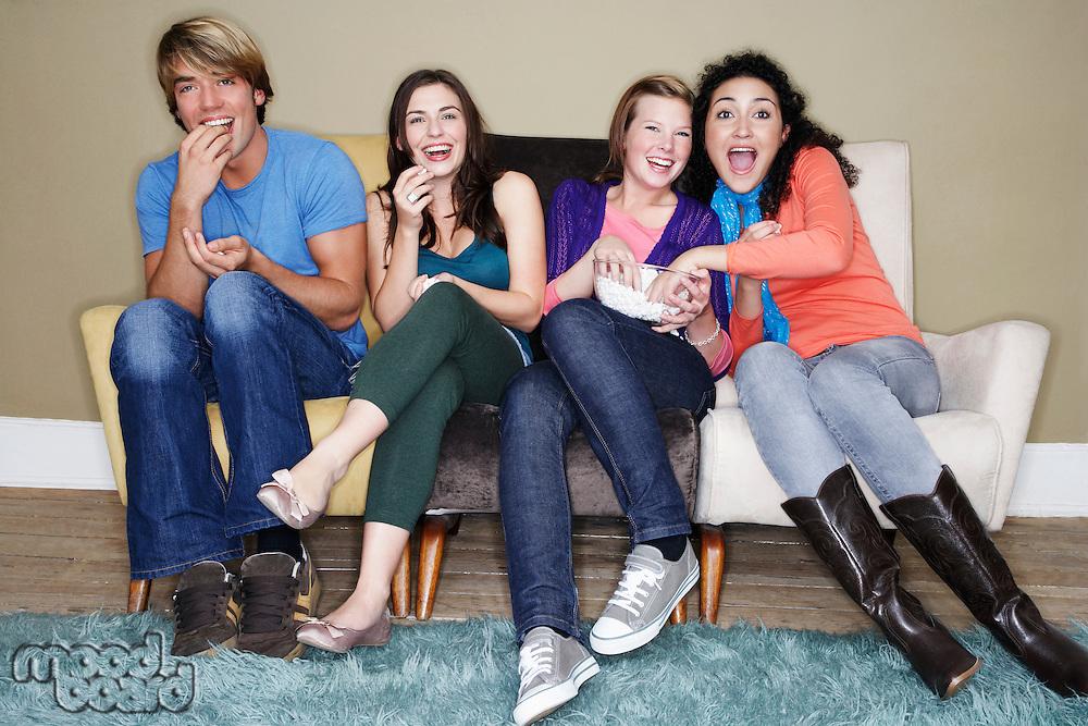 Friends sitting eating popcorn watching movie on sofa