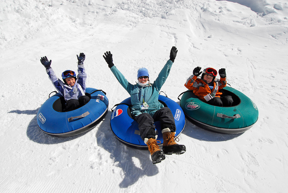 Idaho. Boise. Tubing Hill at Bogus Basin Resort. Mother and young boy and girl having some winter fun. MR family