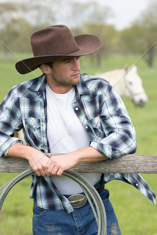 rugged cowboy holding a lasso and leaning on a wooden fence post on a horse ranch