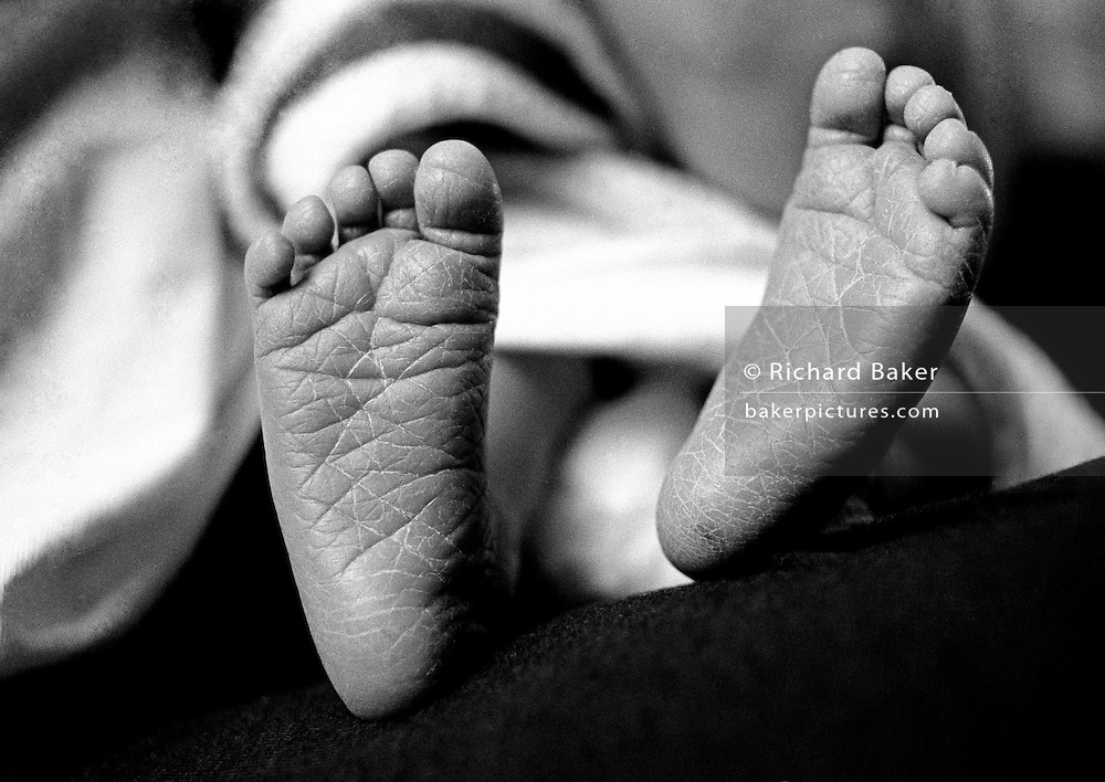 """""""No Distance Covered."""" The leathery soles of a new-born 3 day-old baby girl's feet are seen in detail. Her skin is wrinkled and cracked despite applying foot lotion to keep them soft. The tiny toes have yet to support her upright body and walk anywhere because she has been at home from hospital for only a few days. This is from a documentary series of pictures about the first year of the photographer's first child Ella. Accompanied by personal reflections and references from various nursery rhymes, this work describes his wife Lynda's journey from expectant to actual motherhood and for Ella - from new-born to one year-old."""