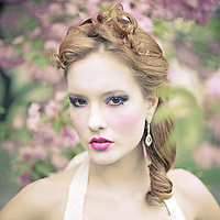 Beautiful young woman in a blurred-out fantasy floral atmosphere.