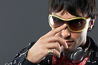 Young man wearing sunglasses and headphones portrait close-up