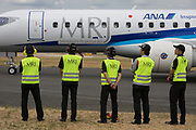 Ground crew with the Japanese airliner manufacturer, Mitsubishi wait for their MRJ (Mitsubishi Regional Jet) with the airline ANA to take off for its fliying demonstration at the Farnborough Airshow, on 18th July 2018, in Farnborough, England.