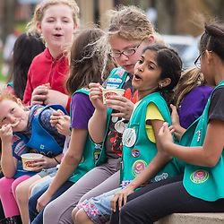 A Girl Scout troupe enjoy some Graeter's ice cream while sitting on a wall outside the store on High Street in Worthington Saturday April 26, 2014. (Christina Paolucci, photographer).