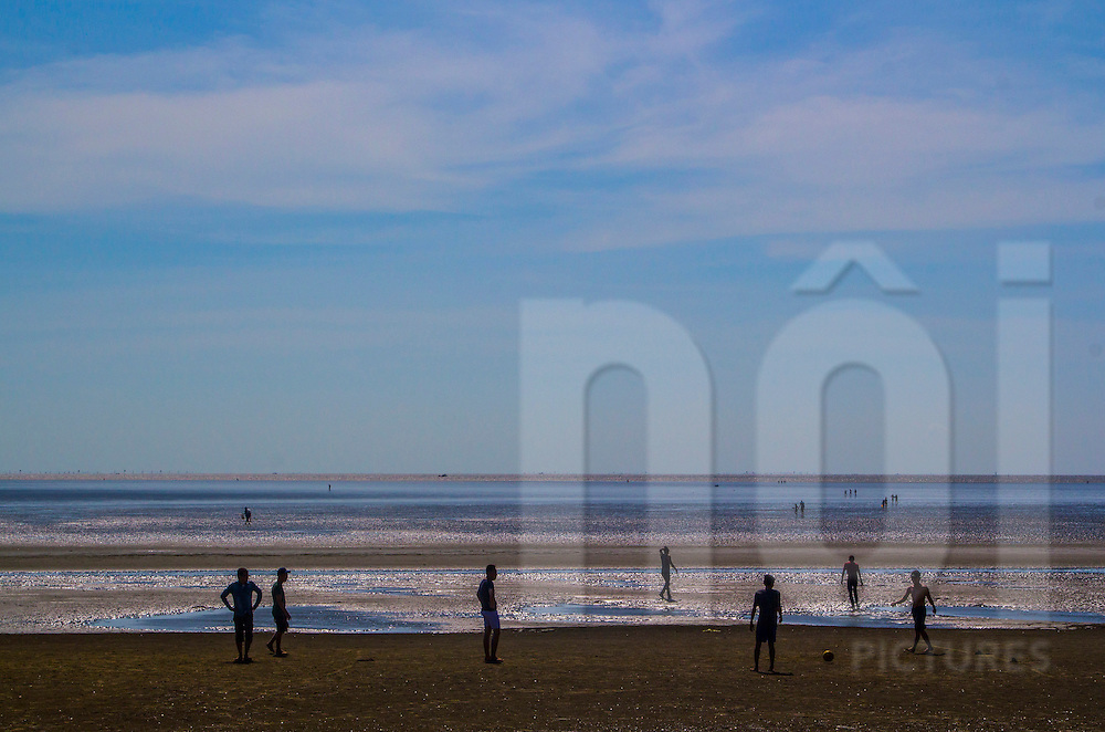 At low tide, friends are playing soccer on a beach. Can Gio, Vietnam, Asia
