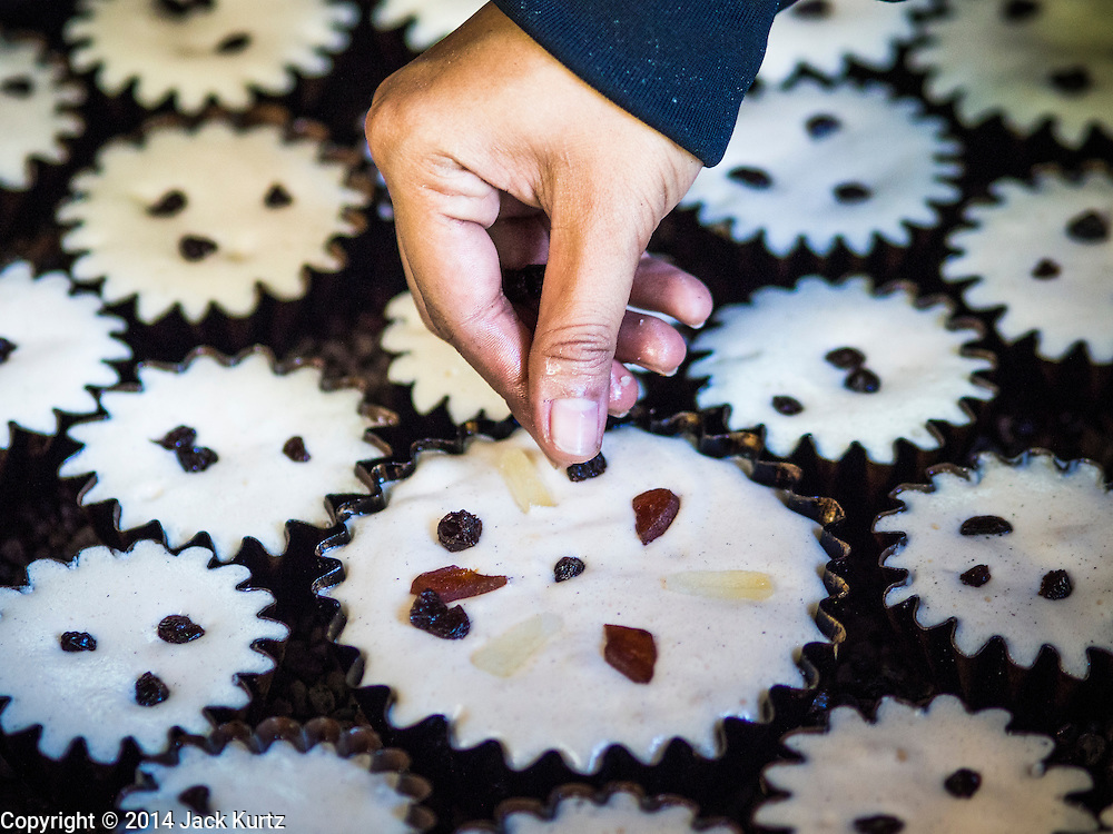 "28 OCTOBER 2014 - BANGKOK, THAILAND: A worker drops raisins on a cake at the Pajonglak Maneeprasit Bakery in Bangkok. The cakes are called ""Kanom Farang Kudeejeen"" or ""Chinese Monk Candy."" The tradition of baking the cakes, about the size of a cupcake or muffin, started in Siam (now Thailand) in the 17th century AD when Portuguese Catholic priests accompanied Portuguese soldiers who assisted the Siamese in their wars with Burma. Several hundred Siamese (Thai) Buddhists converted to Catholicism and started baking the cakes. When the Siamese Empire in Ayutthaya was sacked by the Burmese the Portuguese and Thai Catholics fled to Thonburi, in what is now Bangkok. The Portuguese established a Catholic church near the new Siamese capital. Now just three families bake the cakes, using a recipe that is 400 years old and contains eggs, wheat flour, sugar, water and raisins. The same family has been baking the cakes at the Pajonglak Maneeprasit Bakery, near Santa Cruz Church, for more than 245 years. There are still a large number of Thai Catholics living in the neighborhood around the church.   PHOTO BY JACK KURTZ"