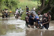 A group of men carry a motorcycle across an overflowing river near the town of Amakpa, Benin on Tuesday September 18, 2007. International NGO Plan said at least 50 villages in Benin had been destroyed by floods that affected at least 1.5 million people in 18 countries across Africa.