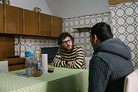 "SUTERA, ITALY - 8 JANUARY 2018: Nunzio Vitellaro (33), the coordinator of the E.U. project working for the NGO ""I Girasoli"", talks with Hussain Munassar, (34), a Pakistani asylum seeker who arrived in Italy in 2015 together with his wife and that were transferred to Sutera in October 2017, here in Sutera, Italy, on January 8th 2018.<br /> <br /> Sutera is an ancient town plastered onto the side of an enormous monolithic rock, topped with a convent, in the middle of the western half of Sicily, about 90 minutes by car south of the Sicilian capital Palermo<br /> Its population fell from 5,000 in 1970 to 1,500 today. In the past 3 years its population has surged  after the local mayor agreed to take in some of the thousands of migrants that have made the dangerous journey from Africa to the Sicily.<br /> <br /> ""Sutera was disappearing,"" says mayor Giuseppe Grizzanti. ""Italians, bound for Germany or England, packed up and left their homes empty. The deaths of inhabitants greatly outnumbered births. Now, thanks to the refugees, we have a chance to revive the city.""<br />  Through an Italian state-funded project called SPRAR (Protection System for Refugees and Asylum Seekers), which in turn is co-funded by the European Union's Fund for the Integration of non-EU Immigrants, Sutera was given financial and resettlement assistance that was co-ordinated by a local non-profit organization called Girasoli (Sunflowers). Girasoli organizes everything from housing and medical care to Italian lessons and psychological counselling for the new settlers.<br /> The school appears to have been the biggest beneficiary of the refugees' arrival, which was kept open thanks to the migrants.<br /> Nunzio Vittarello, the coordinator of the E.U. project working for the NGO ""I Girasoli"" says that there are 50 families in Sutera at the moment."