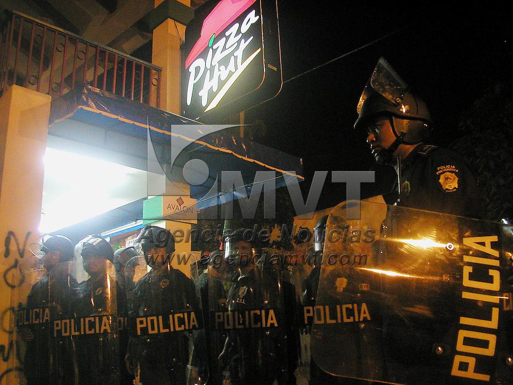 Cancun, M&eacute;x.- Policias antimotimotines resguardan un establecimiento de comida con firma americana el cual fue da&ntilde;ado por un grupo de jovenes encapuchados que protestan en contra de los trabajos de la cumbre de la Organizacion Mundial de Comercio OMC que se desarrolla en esta ciudad. Agencia MVT / Mario Vazquez de la Torre. (DIGITAL)<br /> <br /> NO ARCHIVAR - NO ARCHIVE