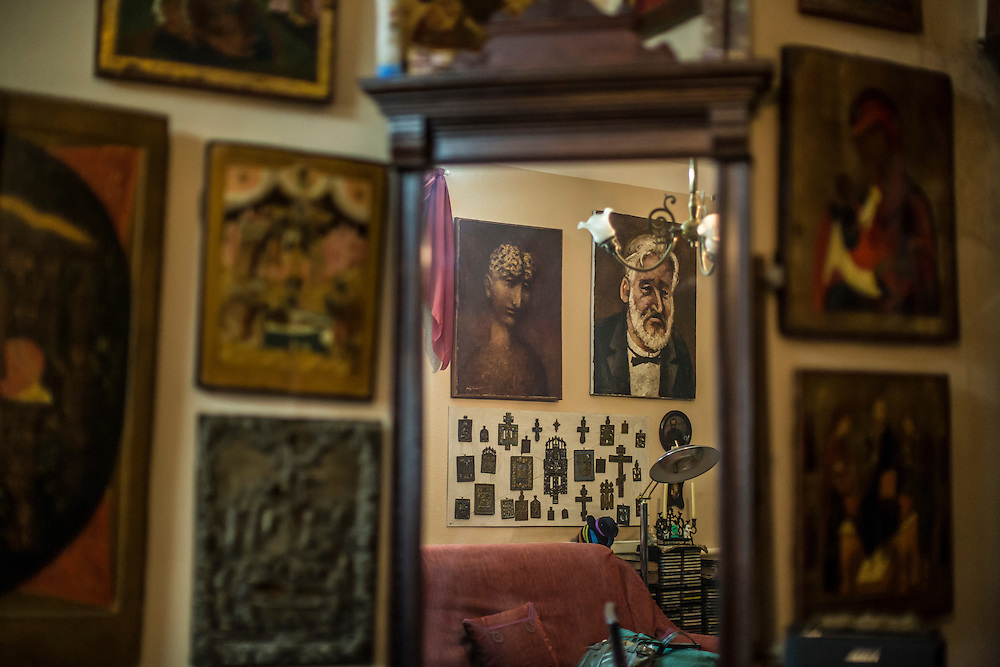 ODESSA, UKRAINE - MARCH 26, 2015: Portraits of poet Boris Khersonsky, painted by friend and artist Aleksandr Roytburd, reflected in a mirror, adorn the walls of his city apartment in Odessa, Ukraine. CREDIT: Brendan Hoffman for The New York Times