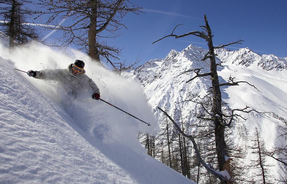 Skier turning in fresh powder snow, Serre Chevalier, France