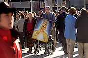 Carolyn Ehli, left, and her father, Andrew Rodiger, both of Moore, Ok., push a painting of Mary in a wheelchair before a Mass by Pope Benedict XVI at National's Stadium in Washington, D.C. on Thursday, April 17, 2008. Carolyn hoped the Pope would bless the painting.   Photo by David Rogowski, AOL