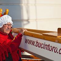 VENICE, ITALY - JANUARY 06: A participant of the Befana Regata helps launching a support boat ahead of the regata on January 6, 2012 in Venice, Italy.  In Italian folklore, Befana is an old woman who delivers gifts to children throughout Italy on the feast of the Epiphany on January 6 in a similar way to Saint Nicholas or Santa Claus.
