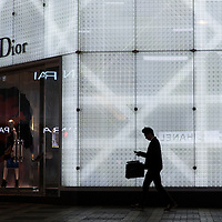 China, Hong Kong, Silhouette of man walking past brightly glowing Dior store in Kowloon Peninsula on winter evening
