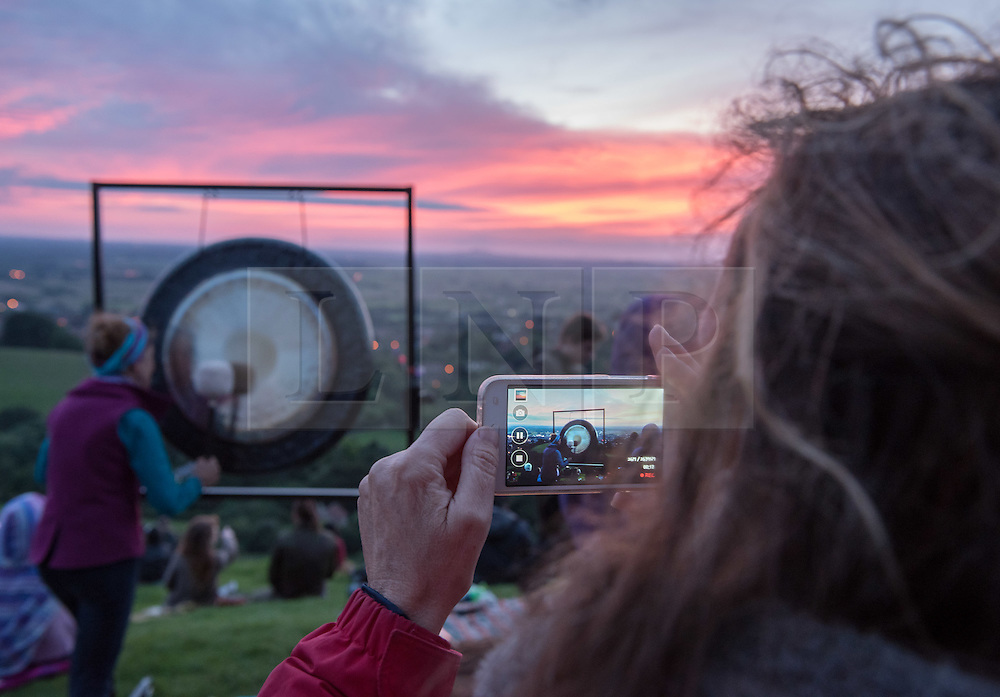 © Licensed to London News Pictures.20/06/2016. Glastonbury, Somerset, UK. A woman plays a gong at sunset on Glastonbury Tor as people prepare to celebrate the Summer Solstice and the shortest night of the year on top of Glastonbury Tor. This year is a leap year and so the actual Solstice fell on 20 June. There was also a 'Strawberry' full moon to coincide with the Solstice, the first time for decades. Photo credit : Simon Chapman/LNP