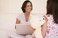 Mother using lap top daughter cuddling teddy sitting on bed