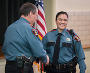 Heather Mariscal, right, is congratulated by Chief Mock after receiving her badge during a swearing-in ceremony for new officers at the Houston ISD Police Department, March 3, 2014.