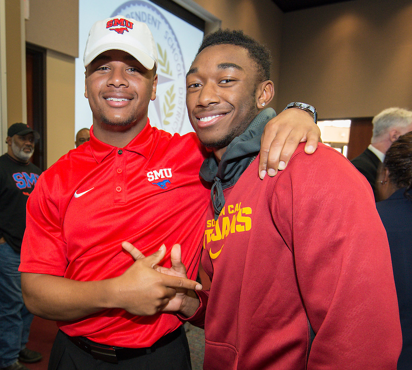Lamar's Darrel Colbert (SMU), left, and John Plattenburg (USC), right, pose for a photograph during a National Signing Day ceremony at the Region 4 Education Center, February 5, 2014.