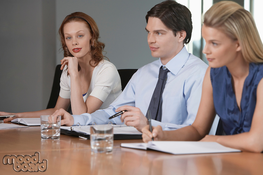 Three businesspeople sitting at business meeting