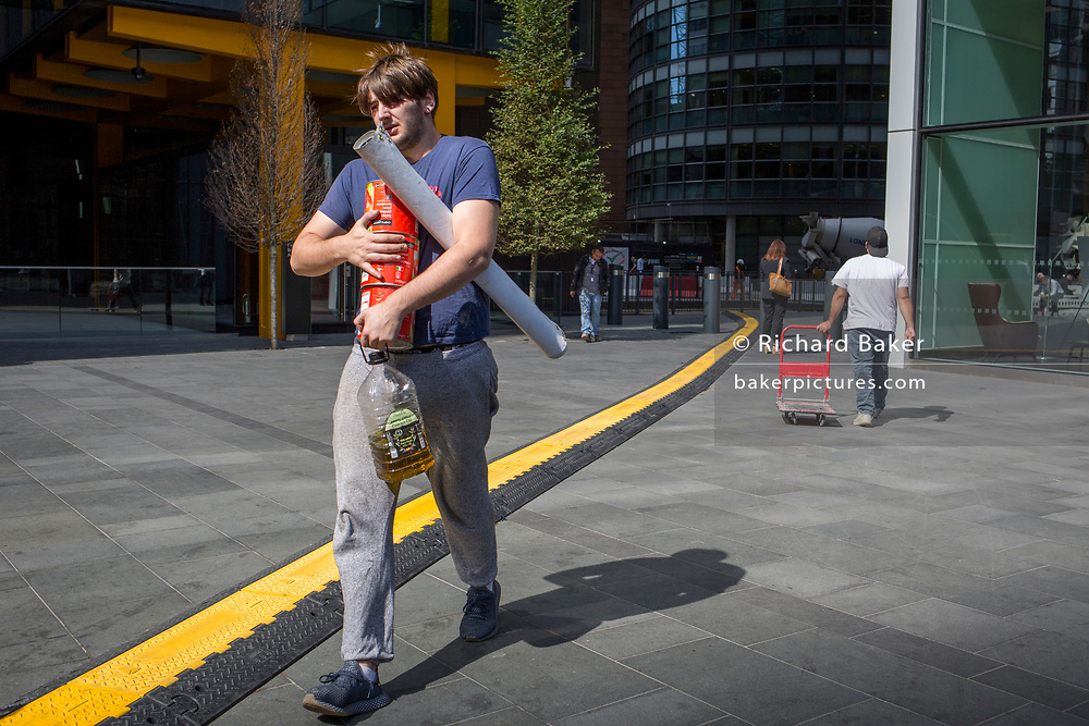 A pop-up catering worker carries supplies alongside a yellow line covering hazardous electrical cabling at Leadenhall in the City of London, (aka The Square Mile) the capital's financial district, on 2nd September 2019, in London, England.