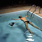 Woman floating in pool facedown.